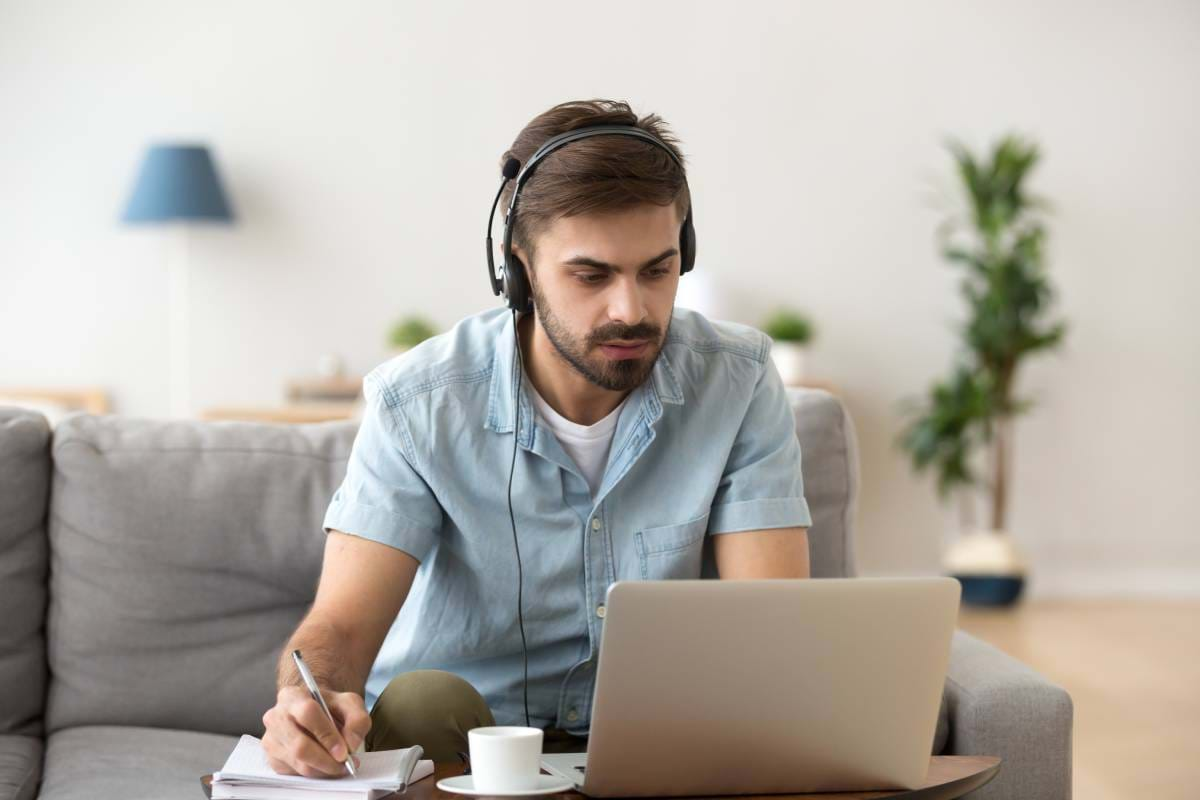 A man working from home using a headset and writing in a notepad