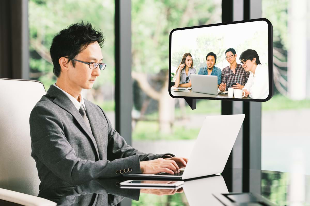 A man in a suit with glasses sitting at a table, video conferencing on his laptop with four other people