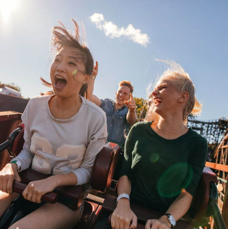 Two Women Laughing While Riding in the Car of a Roller Coaster